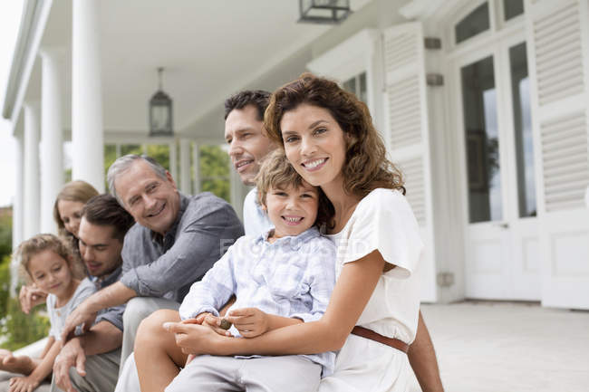 Happy family relaxing on porch together — Stock Photo