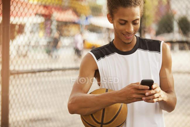 Человек, использующий мобильный телефон на баскетбольной площадке — стоковое фото