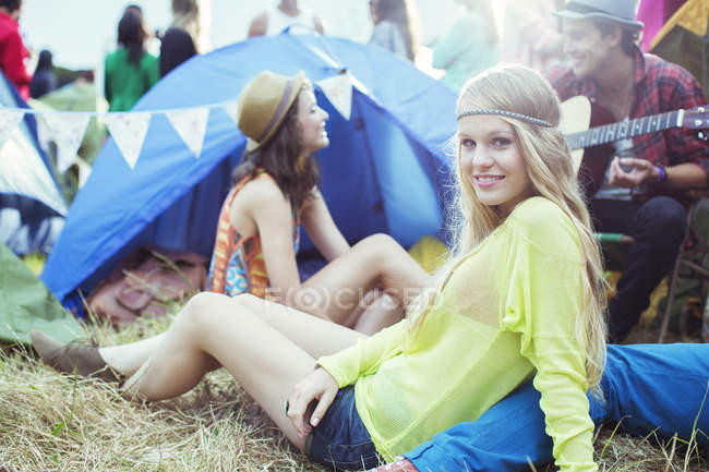 Portrait of woman hanging out with friends outside tent at music festival — Stock Photo