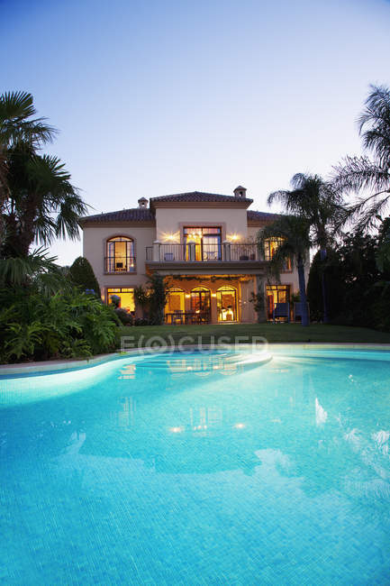Luxury swimming pool and villa at dusk — Stock Photo