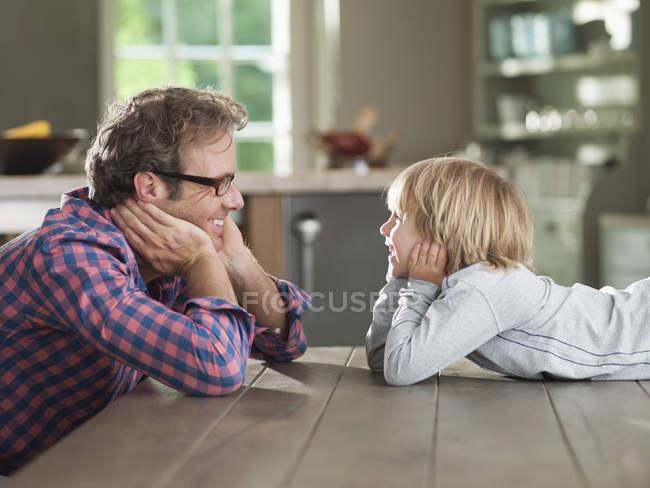 Padre e hijo admirando unos a otros en la mesa - foto de stock