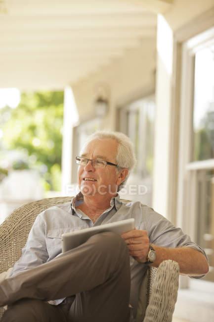 Smiling senior man using digital tablet on porch — Stock Photo