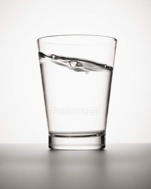 Water sloshing in glass on white background — Stock Photo