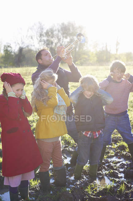 Children covering ears while father playing trumpet — Stock Photo