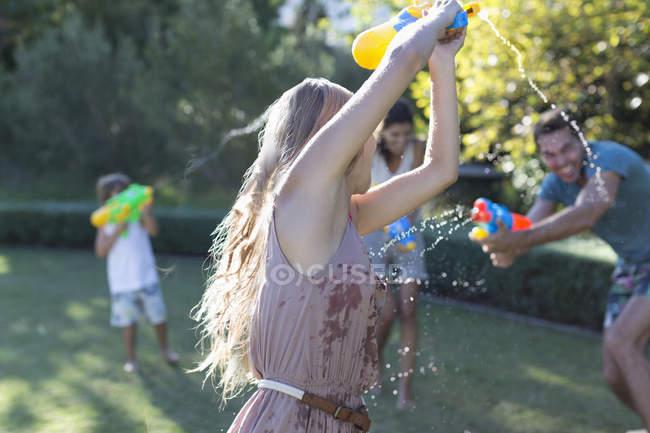 Famiglia che gioca con pistole ad acqua in cortile — Foto stock