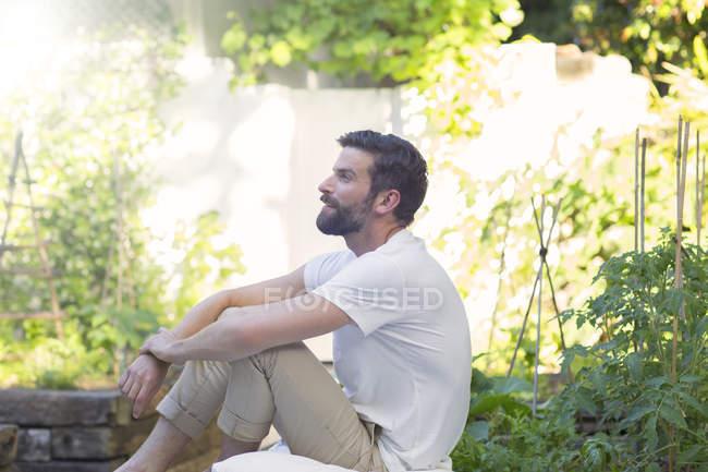 Усміхнений чоловік розслаблюючим у дворі — стокове фото