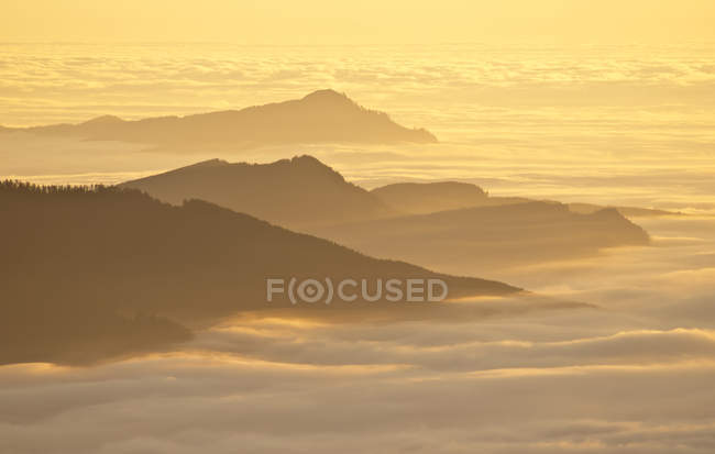 Veduta aerea delle cime delle montagne sopra le nuvole al tramonto — Foto stock