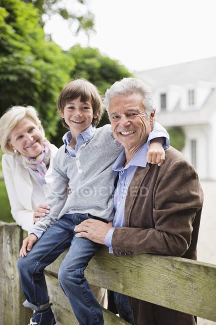 Пара и внук улыбаются через деревянный забор — стоковое фото