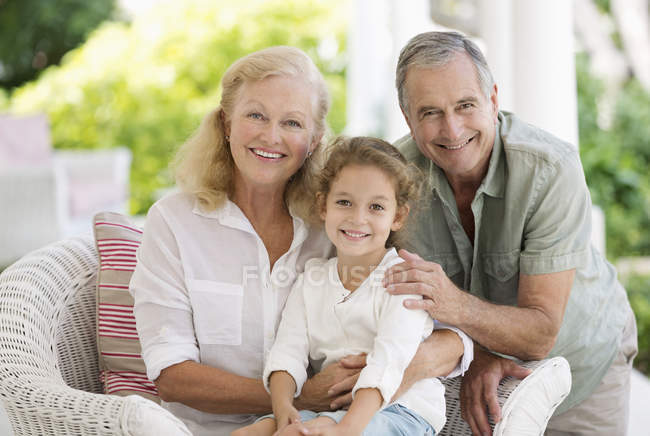Older couple with granddaughter on porch — Stock Photo