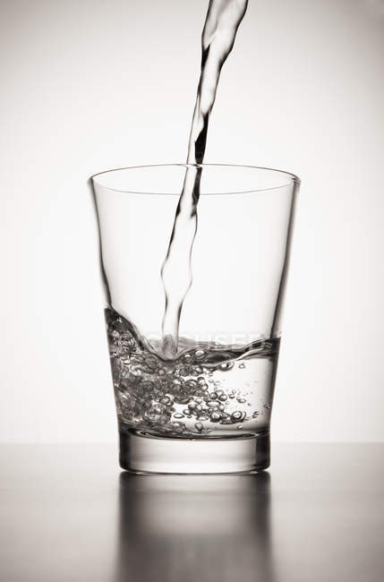 Water pouring into glass on white background — Stock Photo
