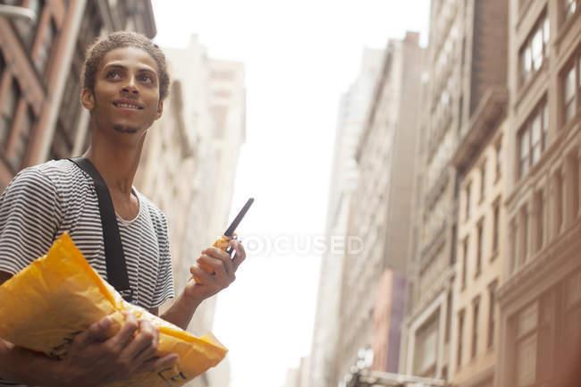 Uomo che trasporta posta sulla strada della città — Foto stock