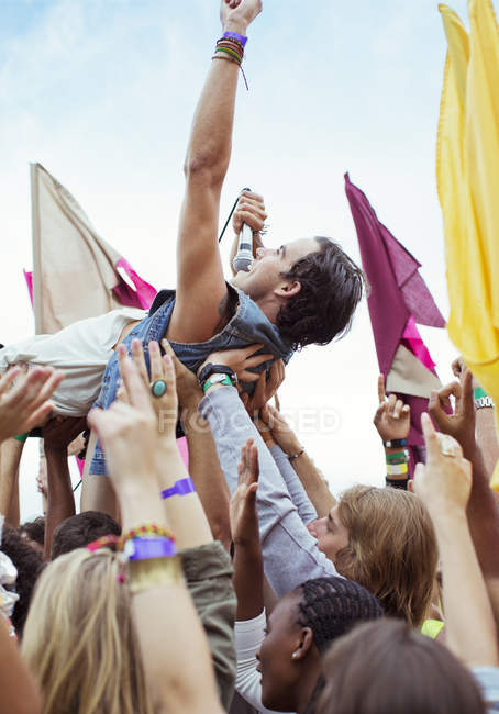 Performer crowd surfing at music festival — Stock Photo