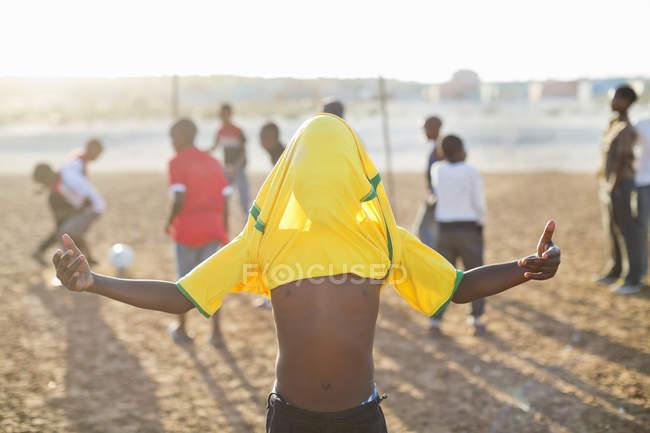 Африканский мальчик празднует с футбольной майкой на голове в грязном поле — стоковое фото