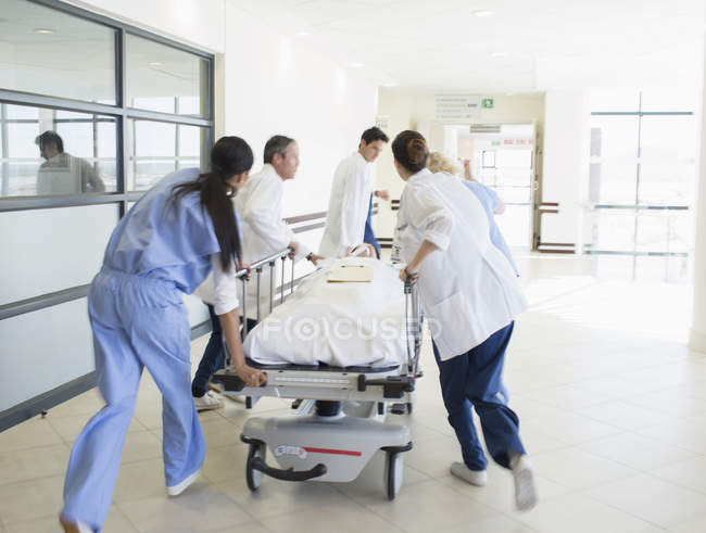 Doctors rushing patient on stretcher down hospital corridor — Stock Photo