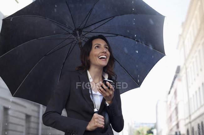 Joyeuse messagerie texte femme d'affaires avec téléphone portable sous parapluie sous la pluie — Photo de stock