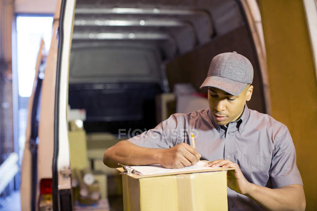 Delivery boy writing on clipboard in van — Stock Photo