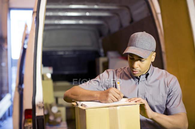 Entrega menino escrevendo na área de transferência em van — Fotografia de Stock