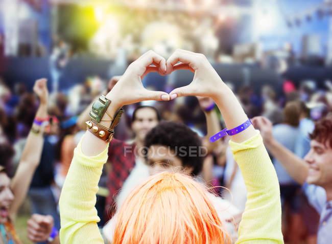 Жінка формування форми серця руками на фестивалі музики — стокове фото