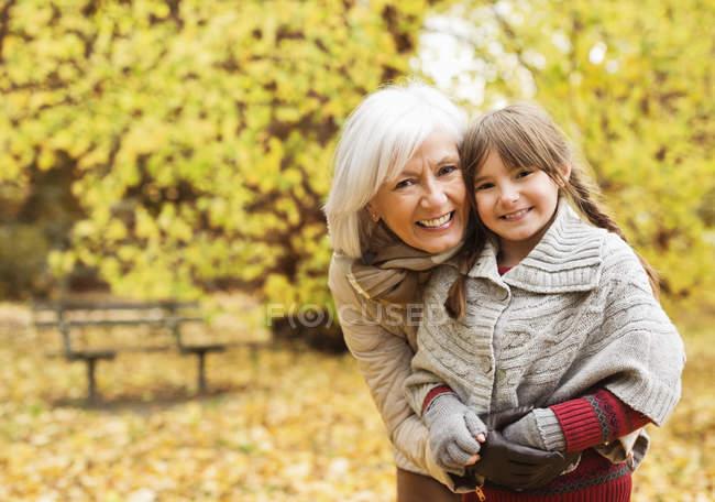 Mujer mayor y nieta sonriendo en el parque - foto de stock