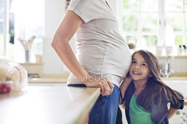 Chica escuchando a las madres embarazadas vientre - foto de stock