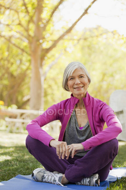 Older woman sitting on yoga mat outdoors — Stock Photo