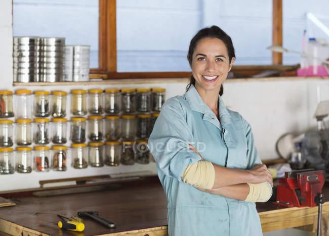 Умелая белая женщина улыбается в мастерской — стоковое фото