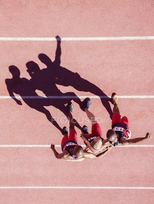 Runners walking with arms around each other on track — Stock Photo