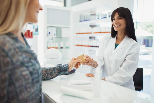 Donna che paga con carta di credito in farmacia — Foto stock