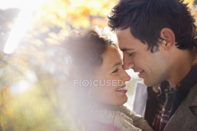 Счастливая кавказская пара обнимается в парке — стоковое фото