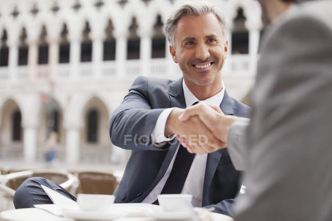 Усміхаючись бізнесменів, потискує руку на тротуарі кафе — стокове фото