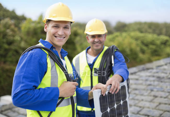 Умелые кавказские рабочие улыбаются на крыше — стоковое фото