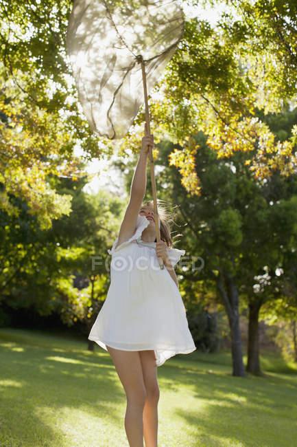 Девушка в платье держит сетку бабочки над головой — стоковое фото