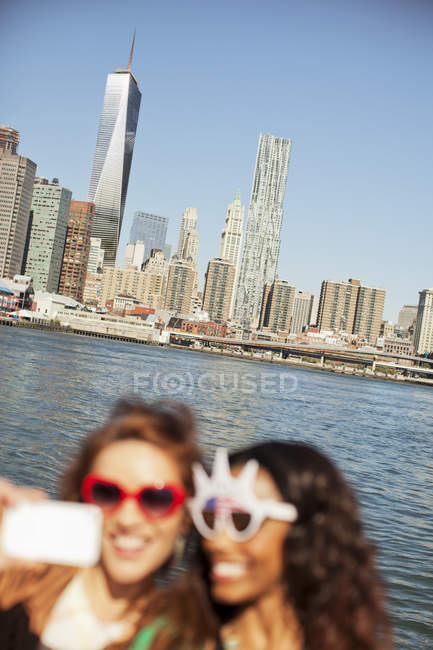 Women in novelty sunglasses taking picture by city cityscape — Stock Photo