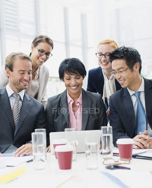 Business people looking at laptop in meeting — Stock Photo