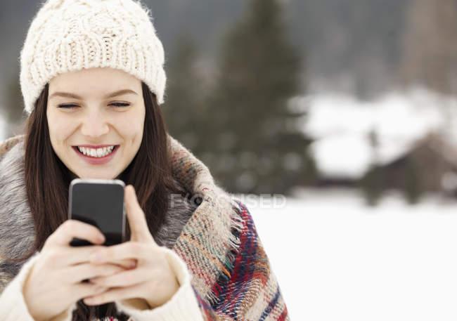 Заделывают женщины в вязать шляпу текстовых сообщений с мобильного телефона — стоковое фото
