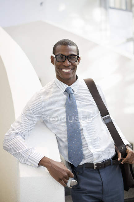 Portrait of smiling businessman on staircase at modern office — Stock Photo