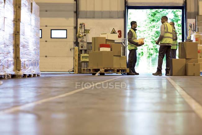 Travailleurs parlant dans un entrepôt — Photo de stock