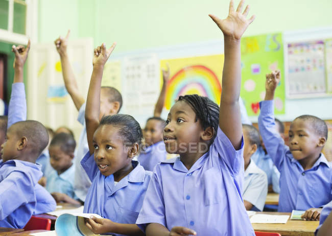 African american students raising hands in class — Stock Photo