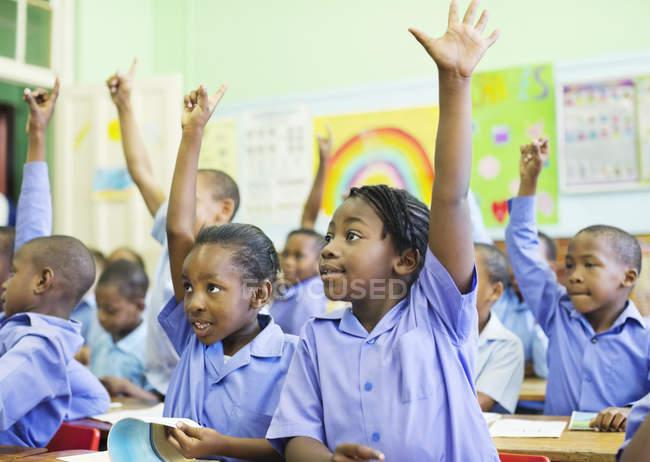 Americanos Africano estudantes levantar as mãos em classe — Fotografia de Stock