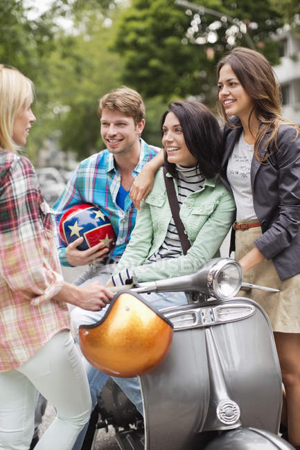 Friends sitting on scooter outdoors — Stock Photo