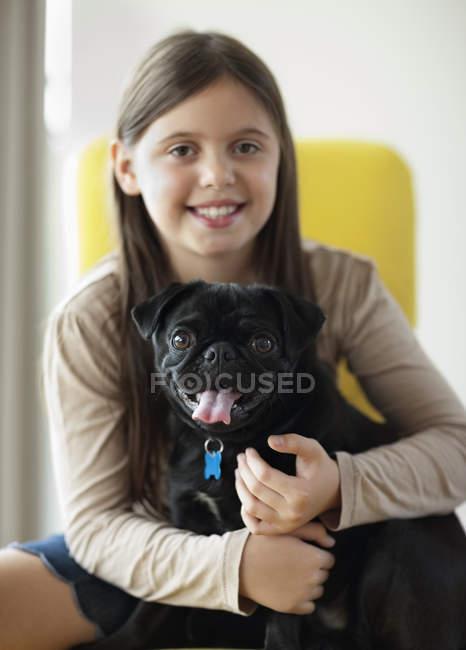 Посміхається дівчина Холдинг собаку в сучасному будинку — стокове фото