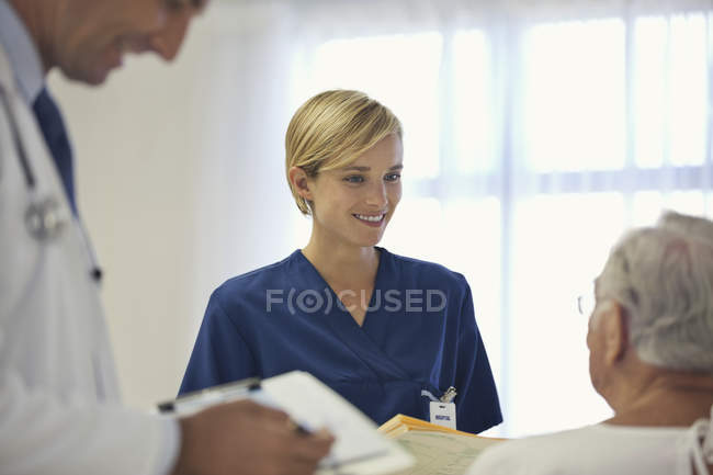 Doctor and nurse talking to older patient in hospital room — Stock Photo