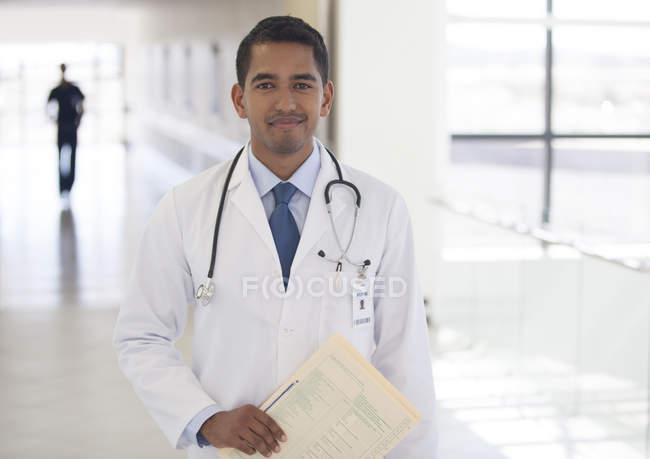 Doutor sorrindo no corredor do hospital moderno — Fotografia de Stock