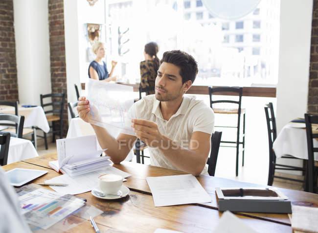 Бизнесмен рассматривает документы в кафе — стоковое фото