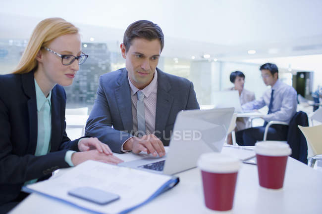 Business people working on laptops at table — Stock Photo