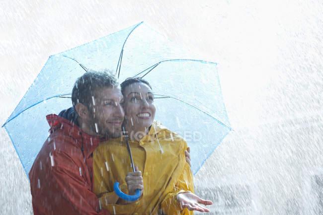 Heureux caucasien couple sous parapluie — Photo de stock