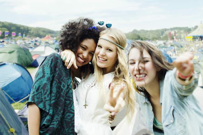 Друзья, обнимающие палатки на музыкальном фестивале — стоковое фото