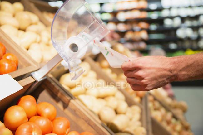 Primo piano dell'uomo che prende il sacchetto di plastica nella sezione dei prodotti del negozio di alimentari — Foto stock