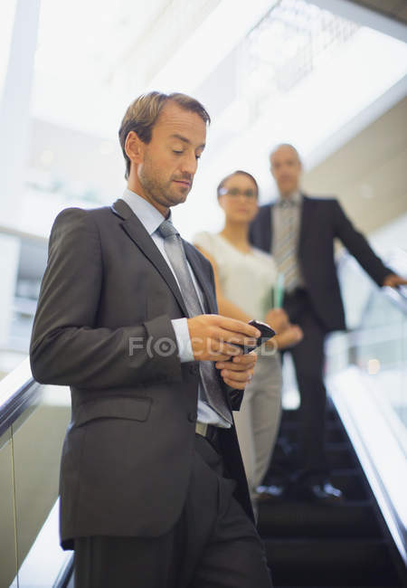 Businessman using cell phone on escalator — Stock Photo