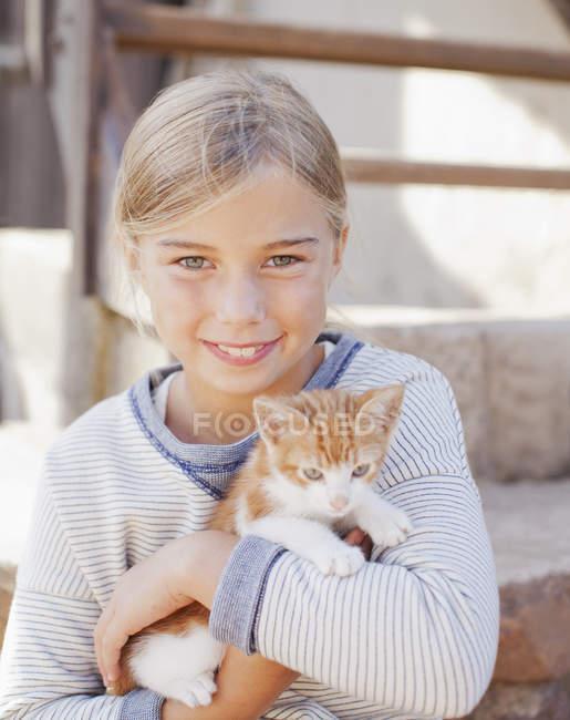 Ritratto di ragazza sorridente che tiene in braccio il gattino — Foto stock